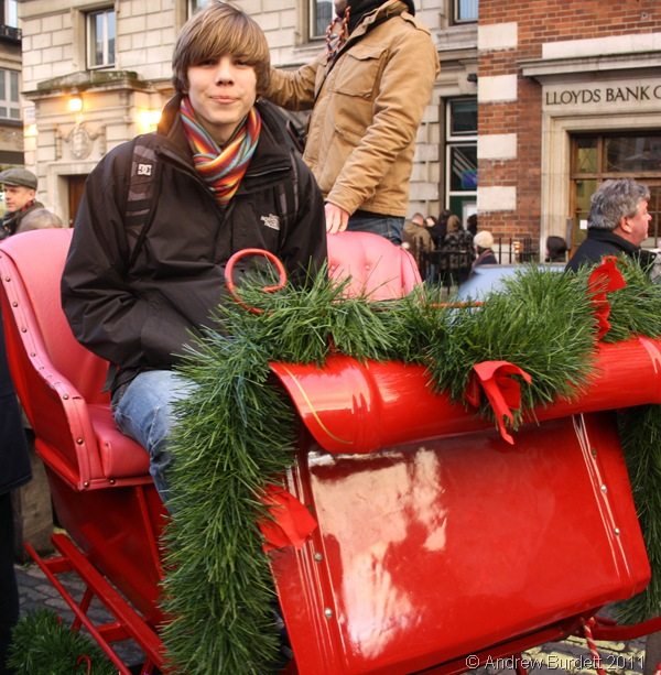 SANTA'S SLEIGH_Zac sits on Father Christmas' sleigh, as offered in Covent Garden.