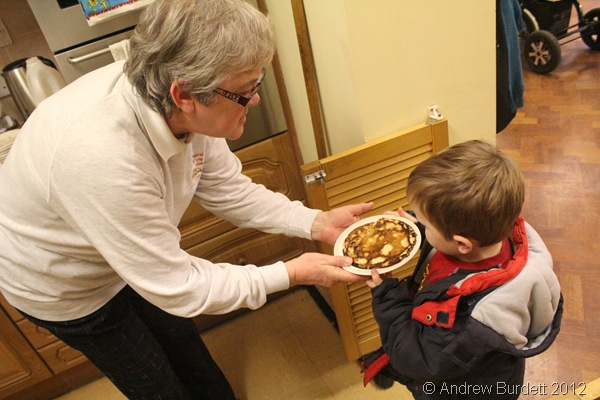 HERE YOU ARE: Sonya presents a child with a pancake. (IMG_8324)
