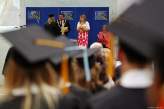 COME ON DOWN: Cllr Andrew Jenner greets one of the Year 11 'graduates' on the stage.