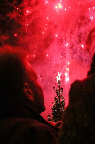 A man looks up at the night's sky, illuminated by red fireworks.