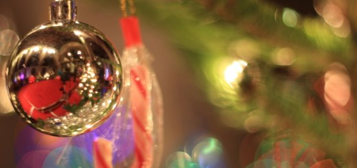 A bauble hangs from a Christmas tree. In it, the interior of St Luke's is visible.