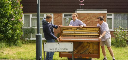 Andrew, Matthew, and Richard Burdett moving the donated piano up the road.