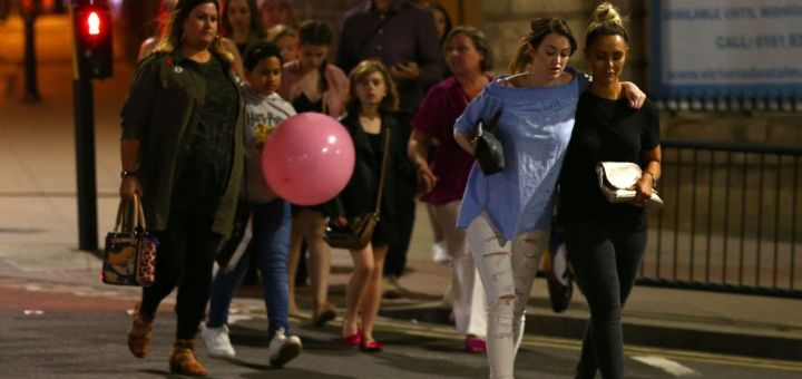 Concert-goers walk away from the Manchester Arena following a bombing there.