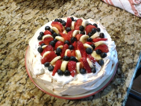 Pavlova topped with berries and bananas