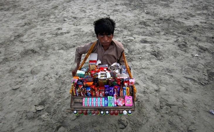 13χρονο αγόρι πουλάει μπισκότα και γλυκά σε παραλία του Πακιστάν.