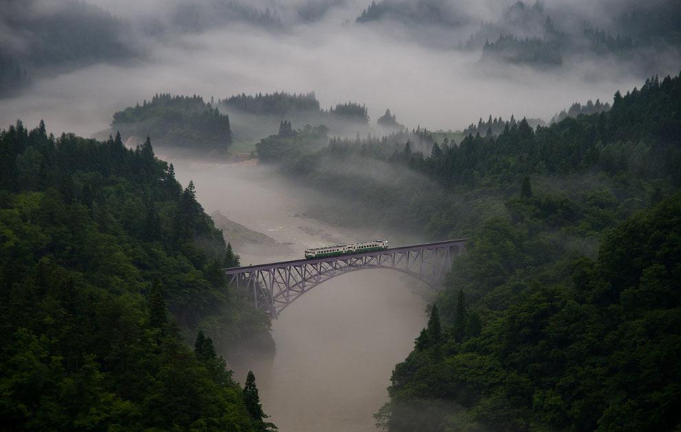 Κοντά στη πόλη Mishima του νομού Fukushima στην Ιαπωνία. Το πρώτο τρένο διασχίζει τη σιδηροδρομική γέφυρα μέσα στην πρωινή ομίχλη. Το τρένο κινείται προς τα εμπρός, λίγο-λίγο, αργά. Σκέφτηκα ότι, αυτό το θέαμα εκφράζει τους κατοίκους της Φουκουσίμα που προσπαθούν να ανακάμψουν από το σεισμό και το πυρηνικό ατύχημα. Μα αυτό είναι ένα αβέβαιο ατελείωτο ταξίδι. (© Teruo Araya