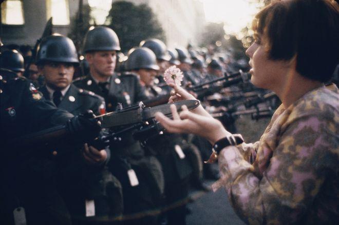 """La Jeune Fille a la Fleur,"" μια φωτογραφία του Marc Riboud που απεικονίζει τη νεαρή ειρηνίστρια, Jane Rose Kasmir, να τοποθετεί ένα άνθος στις ξιφολόγχες της φρουράς του Πενταγώνου, κατά τη διάρκεια διαμαρτυρίας για τον πόλεμο στο Βιετνάμ (21 Οκτωβρίου 1967). Η φωτογραφία θα γίνει το σύμβολο του ""κινήματος των λουλουδιών""."