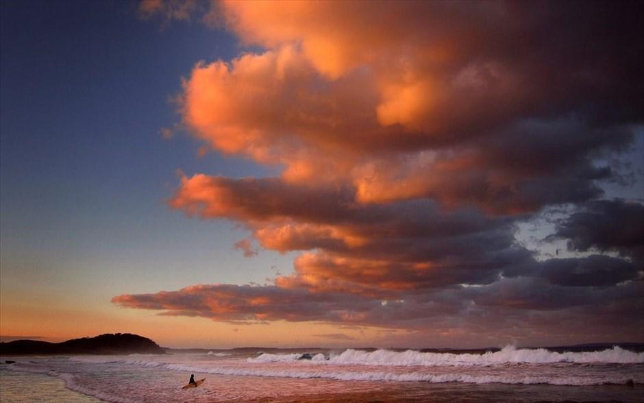 Μία αθλήτρια του σέρφινγκ, κρατώντας τη σανίδα της, περιμένει το κατάλληλο κύμα, καθώς τα σύννεφα χρωματίζονται από τον ήλιο που δύει στην παραλία Mollymook της Νέας Νότιας Ουαλίας.