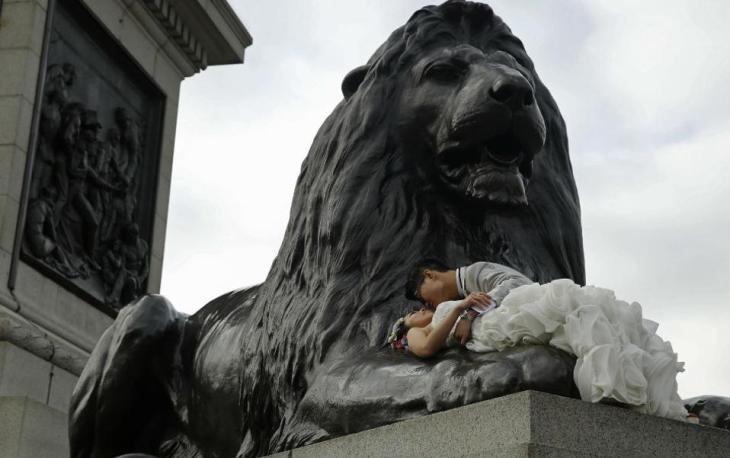 Κινέζοι στο Λονδίνο. Κάθε διεθνές μνημείο είναι τελικά ιδανικό φόντο για τις γαμήλιες φωτογραφίες των Κινέζων. Έτσι και το ζευγάρι της φωτογραφίας ταξίδεψε μέχρι το Λονδίνο για να ξαπλώσει πάνω σε ένα από τα λιοντάρια της πλατείας Trafalgar. REUTERS/Luke MacGregor