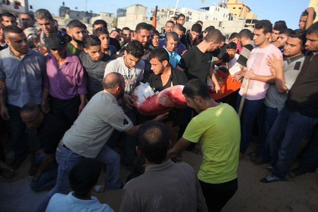 Mourners carry the body of one of four Palestinians from the Juda family, whom medics said were killed in an Israeli air strike