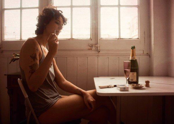 キッチンでタバコを吸う女性
