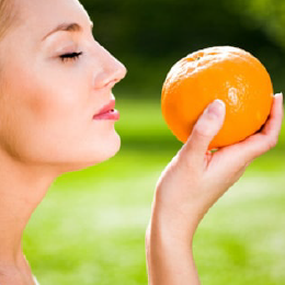 Woman smelling the scent out of an orange