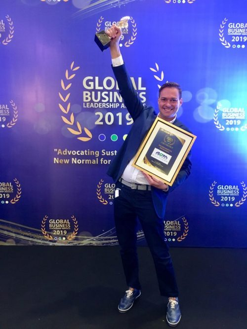 AOM Philippines CEO Jeroen holding trophy for environmental excellence award