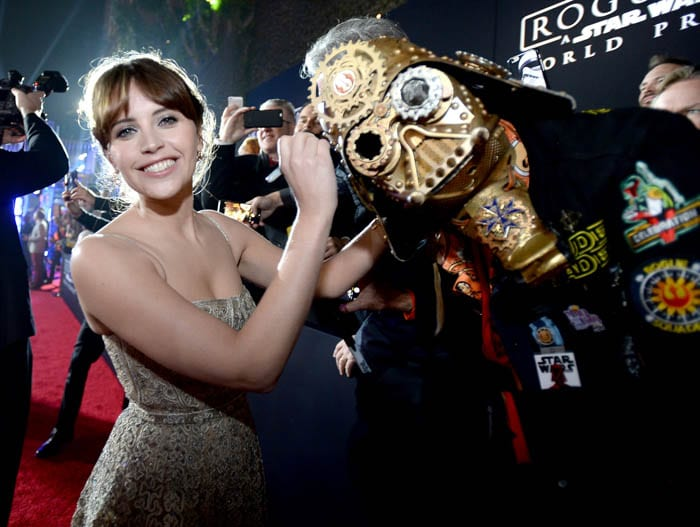 "HOLLYWOOD, CA - DECEMBER 10: Actress Felicity Jones (L) signs Christopher 'Dude Vader' Canole's helmet at The World Premiere of Lucasfilm's highly anticipated, first-ever, standalone Star Wars adventure, ""Rogue One: A Star Wars Story"" at the Pantages Theatre on December 10, 2016 in Hollywood, California. (Photo by Charley Gallay/Getty Images for Disney) *** Local Caption *** Felicity Jones; Christopher Canole"