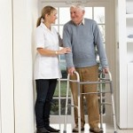 A physiotherapist treating an elderly person at home