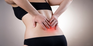 Pain in back of women on gray background. Caring for the female body. Red dot
