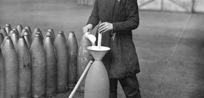 A munitions worker fills a shell at the National Filling Factory at Banbury. She is using a funnel and a scoop to pour the powder into the shell.