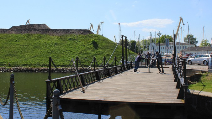 Two men mechanically rotating a bridge in Klaipeda with the Klaipeda Fort in the background.