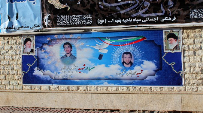 A poster of the Supreme Leaders of Iran and two assassinated nuclear scientists on the wall of a building.