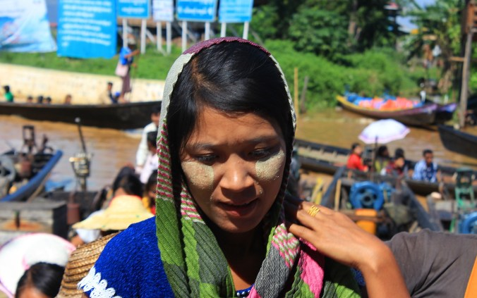 Burma / Myanmar in pictures. A young and beautiful Myanmar woman with thanaka face paint on her cheeks by the Inle Lake.