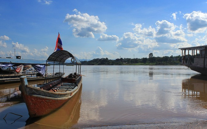 What travel teaches you about life and happiness? A slowboat on the coast of Mekong River in Huay Xai, Laos, with blue sky in the background.