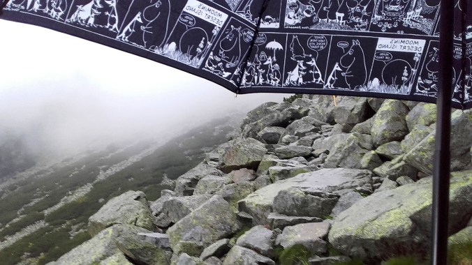 A black and white Moomin comic umbrella on a rocky mountain path.