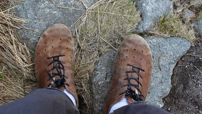 Tips for traveler's day hikes. Worn Ecco Biom leather shoes on rock.