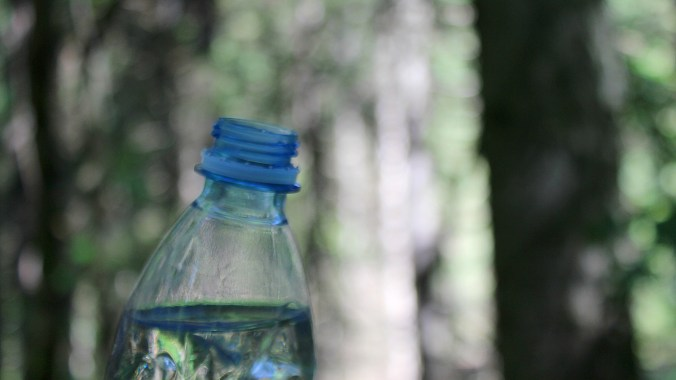 An open bottle of water with a blurry forest background.