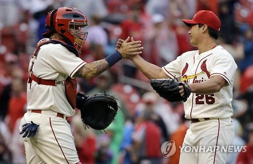 St. Louis Cardinals' relief pitcher Oh Seung-hwan (R) celebrates his first major league save with catcher Yadier Molina against the Milwaukee Brewers in St. Louis in this Associated Press photo on July 2, 2016. (Yonhap)