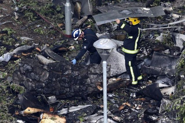 Firefighters inspect the blackened interior of Grenfell Tower