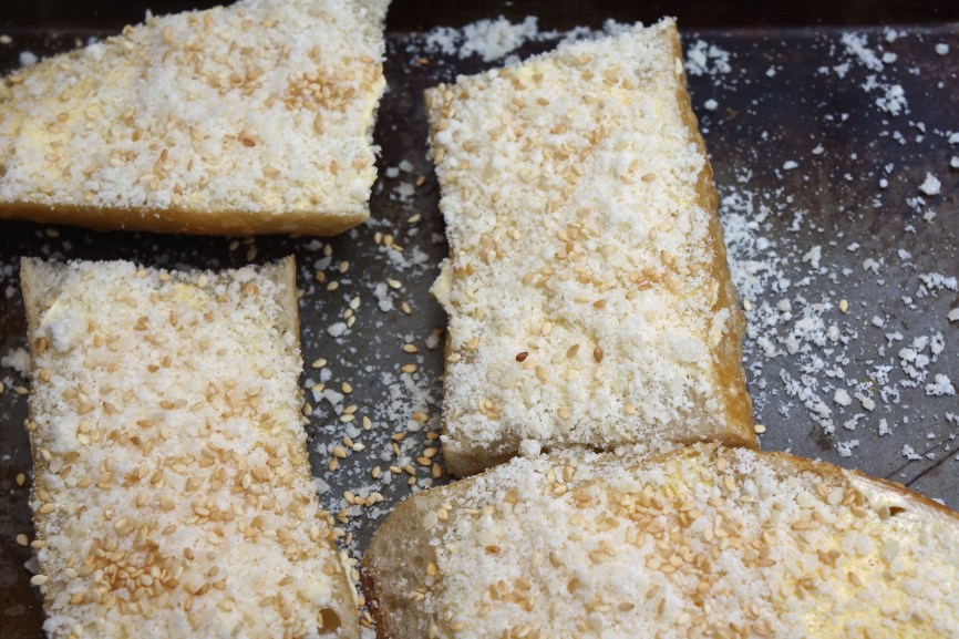Top each piece with granulated garlic, kosher salt, Parmesan cheese and sesame seeds (if using).