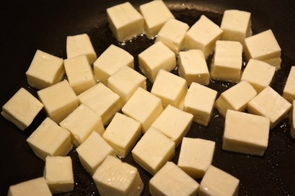 In a separate skillet over medium high heat, warm 1 tablespoon of oil. Add cubed paneer and cook until golden, turning frequently.
