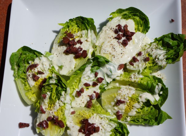 Drizzle lettuce with dressing. Top with chopped olives and serve.