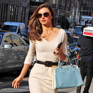 Miranda Kerr out in a tight cream dress and light blue Prada hand bag