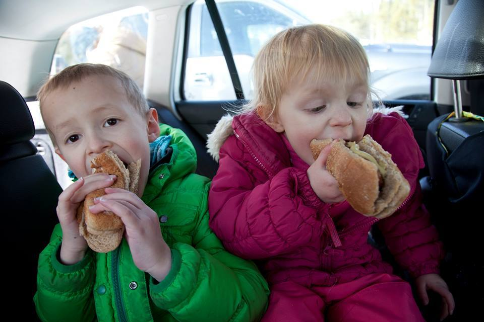 Kids eating hotdogs in the car.