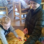 Playing checkers at the lodge. (Cooper drew his own checkerboard and tries to play with buttons, so this made his day.)
