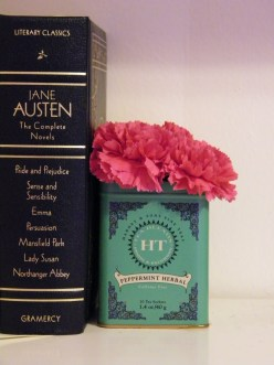 Jane Austen perched on my bookshelf with a DIY tea tin vase.
