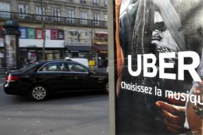 A taxi passes by an advertisement for the Uber car and ride-sharing service displayed on a bus stop in Paris, France, in this March 11, 2016 file photo. REUTERS/Charles Platiau/File Photo