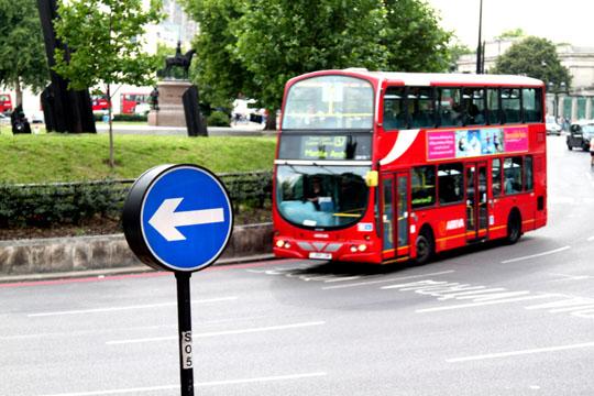 London Left Arrow Sign And Double Decker Bus
