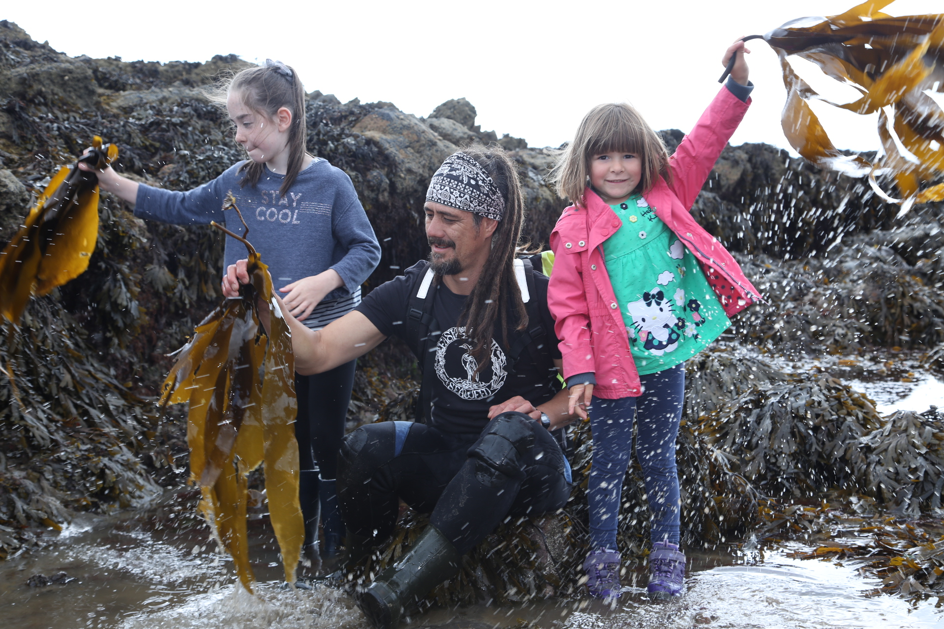 Seaweed forager Jayson Byles shows local children his craft in Fife's East Neuk