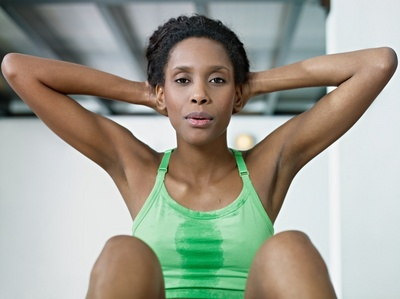 young african american woman in green sportswear exercising abdominals in fitness club, looking at camera. Horizontal shape, front view, waist up