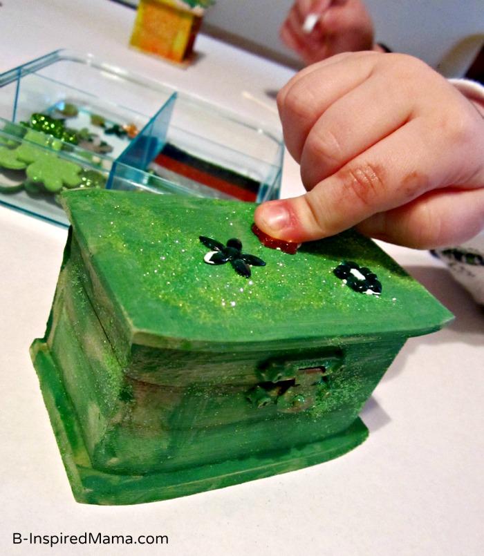 Kid Gluing their St. Patrick Craft Leprechaun Trap Box at B-InspiredMama.com