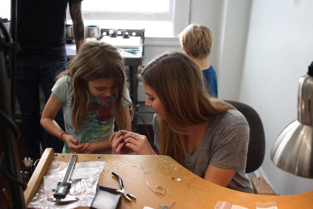 Alexei's assistant, Anna, shows Erin some metal that will be made into a ring.