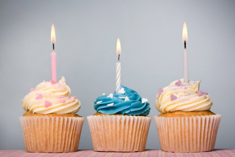 Trio of cupcakes decorated with frosting and candles