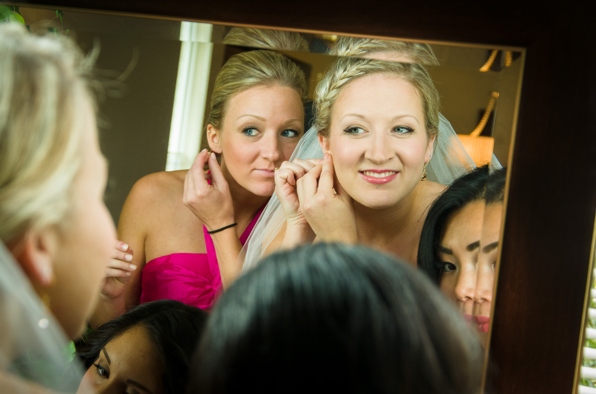 Bride and bridesmaids getting ready looking in mirror
