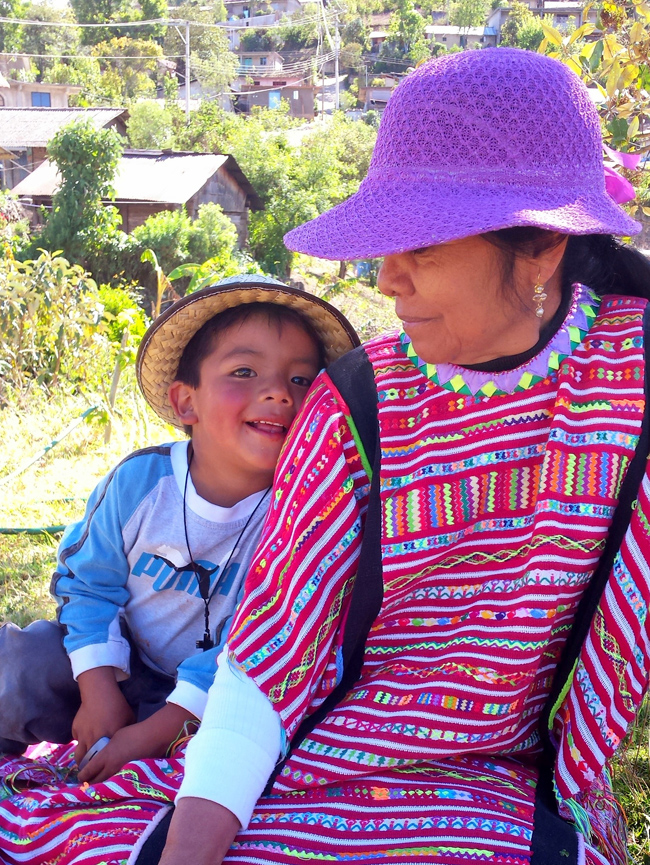 Boy snuggles into his grandmother who wears traditional woven huipil of the Triqui indigenous people.