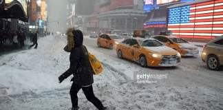 Pedestrians cope with snow covering sidewalks and streets in Time Square on January 23, 2016 in New York City. A major Nor'easter is hitting much of the East Coast and parts of the South as forecasts warn of up to two feet of snow in some areas. January 23, 2016| Credit: Astrid Riecken