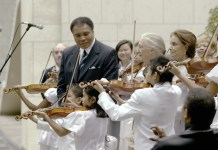 "Shown here is UN "" Messenger of Peace"", Muhammad Ali, center, together with the young Tarumi Violinists, under the direction of Yukako Tarumi, who performed on the International Day of Peace on September 21, 2004. UN Messengers of Peace, conservationist Jane Goodall, and author/ journalist Anna Cataldi, participated in this event, as well. This photo was published in the book ""The United Nations at 70. MOMENTS AND MILESTONES"" (Lifetouch family of photographers) and on display in a photo exhibit at UN Headquarters documenting the history of the United Nations. UN Photo/Ki Chung."