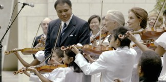"""Shown here is UN """" Messenger of Peace"""", Muhammad Ali, center, together with the young Tarumi Violinists, under the direction of Yukako Tarumi, who performed on the International Day of Peace on September 21, 2004. UN Messengers of Peace, conservationist Jane Goodall, and author/ journalist Anna Cataldi, participated in this event, as well. This photo was published in the book """"The United Nations at 70. MOMENTS AND MILESTONES"""" (Lifetouch family of photographers) and on display in a photo exhibit at UN Headquarters documenting the history of the United Nations. UN Photo/Ki Chung."""