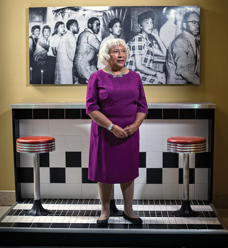 Helena Hicks, at Morgan, in front of a sit-in photo from Arundel Ice Cream. Photograph Christopher Myers, courtesy Baltimore Magazine.